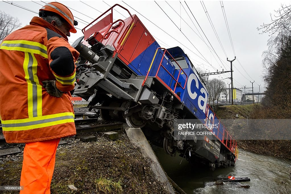 A diesel locomotive has ended up in the river Venoge on March 8, 2013 near Penthalaz, Western Switzerland. The freight locomotive derailed near Cossonez railway station with its driver slightly injured. AFP PHOTO / FABRICE COFFRINI