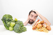 Diet decision and nutrition choices dilemma between healthy good fresh fruit and vegetables or greasy cholesterol rich fast food with a puzzled man trying to decide what to eat.