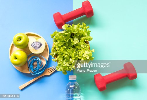 Diet slimming weight with green apple and measuring tap, scale weight on the wood plate, vegetables, dumbbells, colourful background.  Diet and Healthy Concept : Stock Photo