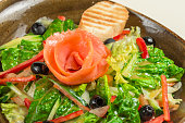 Dietary salad of bell pepper, lettuce, cucumber, olives and olive oil, a slice of bread. In the middle of the dish is a rose flower-of red fish - salmon