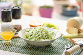 Dietary vegetarian japanese salad made from daikon radish, celery, cucumber and spring onions in a plate and with ingredients on the table - an organic dish