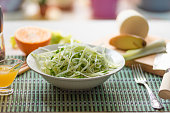 Dietary vegetarian salad made from daikon radish, celery, cucumber and spring onions in a plate and with ingredients on the table - an organic dish