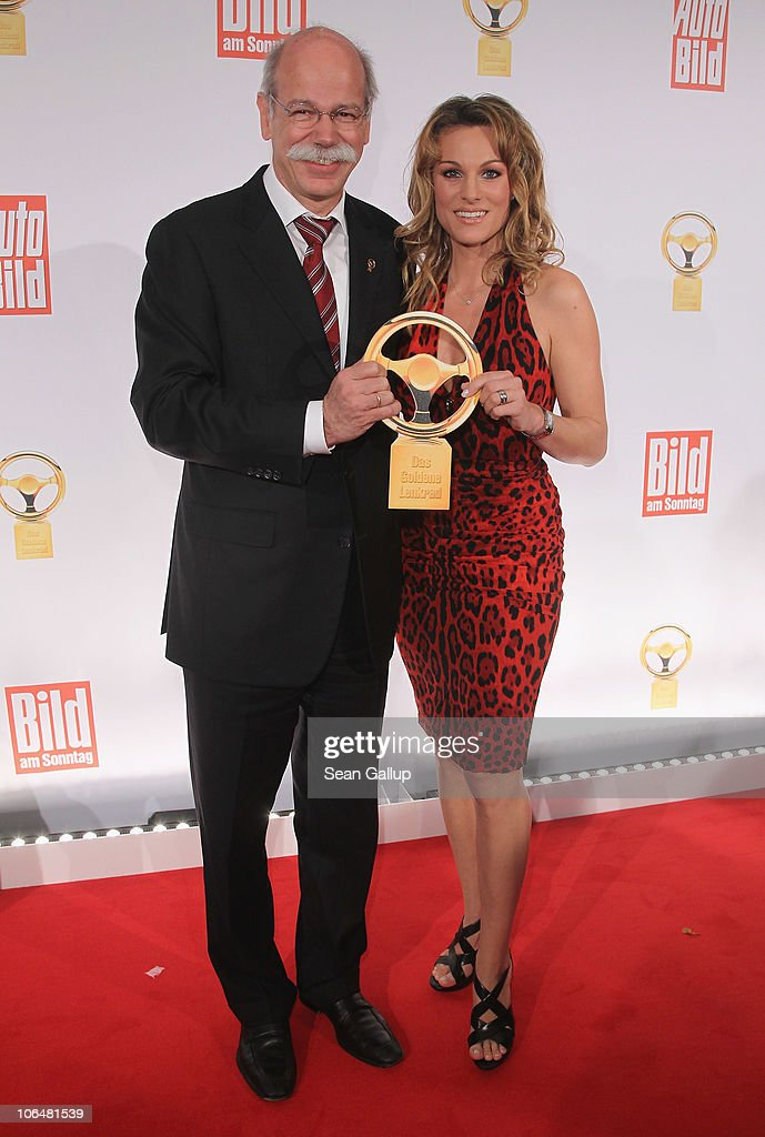 Dieter Zetsche, Chairman of Daimler AG, and race care driver Christina Surer attend the 2010 Das Goldene Lenkrad awards at Axel Springer Haus on November 3, 2010 in Berlin, Germany.