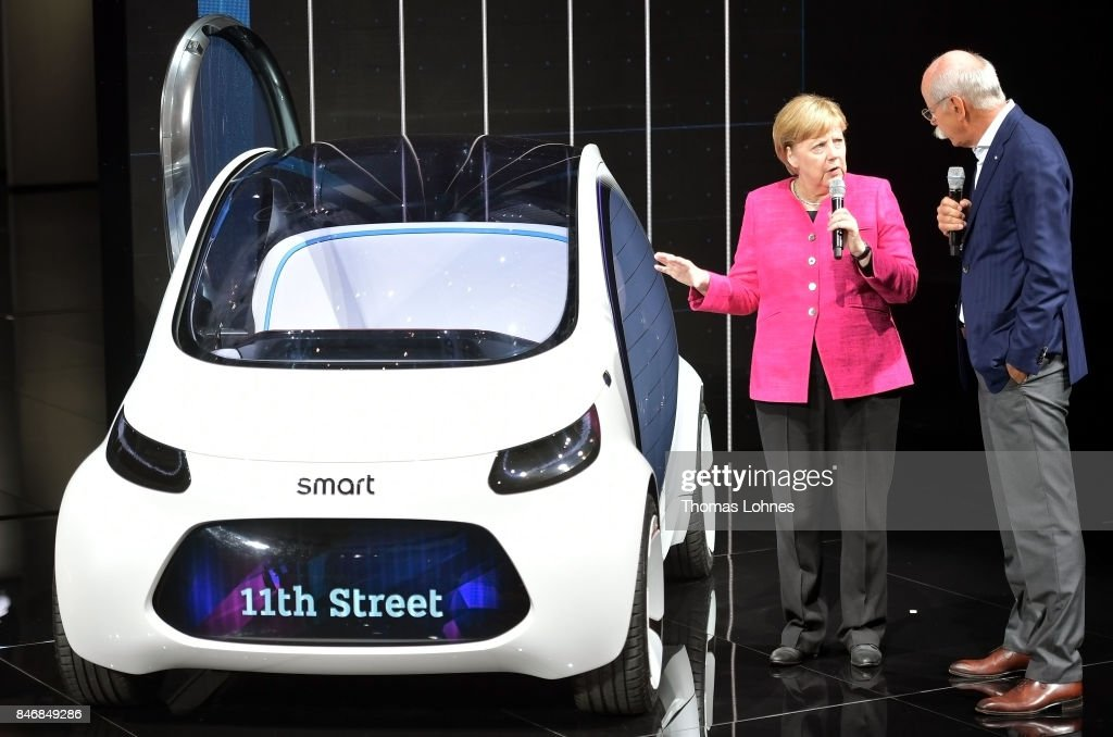 Dieter Zetsche, Chairman of Daimler AG, shows the German Chancellor Angela Merkel a Smart Vision EQ concept car during her visit at the 2017 Frankfurt Auto Show 'Internationale Automobil Ausstellung' (IAA) on September 14, 2017 in Frankfurt am Main, Germany. The Frankfurt Auto Show is taking place during a turbulent period for the auto industry. Leading companies have been rocked by the self-inflicted diesel emissions scandal. At the same time the industry is on the verge of a new era as automakers commit themselves more and more to a future that will one day be dominated by electric cars.