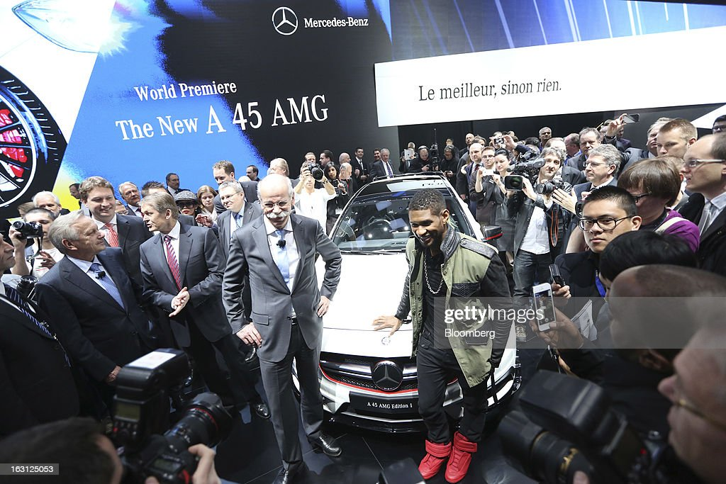Dieter Zetsche, chief executive officer of Daimler AG, center left, stands with American singer Usher, center right, at the launch of the Mercedes-Benz A 45 AMG automobile, produced by Daimler AG, on the first day of the 83rd Geneva International Motor Show in Geneva, Switzerland, on Tuesday, March 5, 2013. This year's show opens to the public on Mar. 7, and is set to feature more than 100 product premiers from the world's automobile manufacturers. Photographer: Chris Ratcliffe/Bloomberg via Getty Images