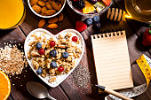 Dieting concept: Top view of a heart shaped bowl filled with yogurt, cereal and berries for a healthy meal on wood table with lined blank notebook beside it.  A tape measure is visible at the bottom-r