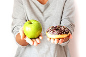 Dieting concept with young woman choosing between healthy fruits and sweets, holding green apple and tasty chocolate donut