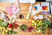 Dietitian holding avocado and olive oil above the table full of various healthy products, ketogenic diet concept