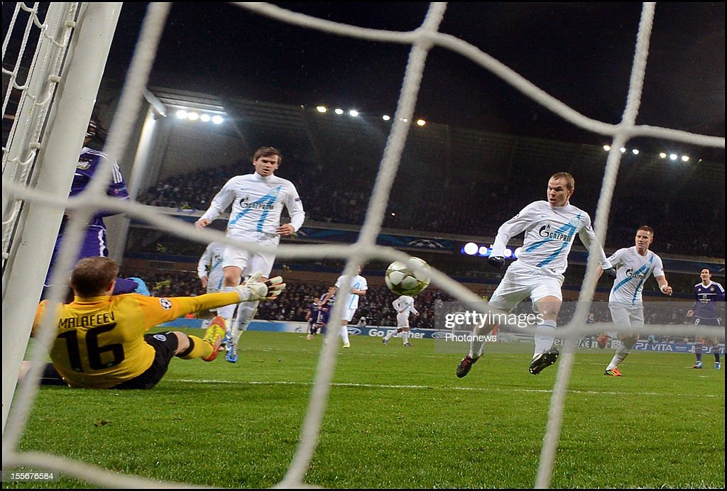 Dieudonne Mbokani of RSC Anderlecht (L) scores the opening goal past FC Zenit St Petersburg goalkeeper <a gi-track='captionPersonalityLinkClicked' href=/galleries/search?phrase=Vyacheslav+Malafeev&family=editorial&specificpeople=3012873 ng-click='$event.stopPropagation()'>Vyacheslav Malafeev</a> during the UEFA Champions League Group C match between RSC Anderlecht and FC Zenit St Petersburg at the Constant Vanden Stock Stadium on November 6, 2012 in Brussels, Belgium.