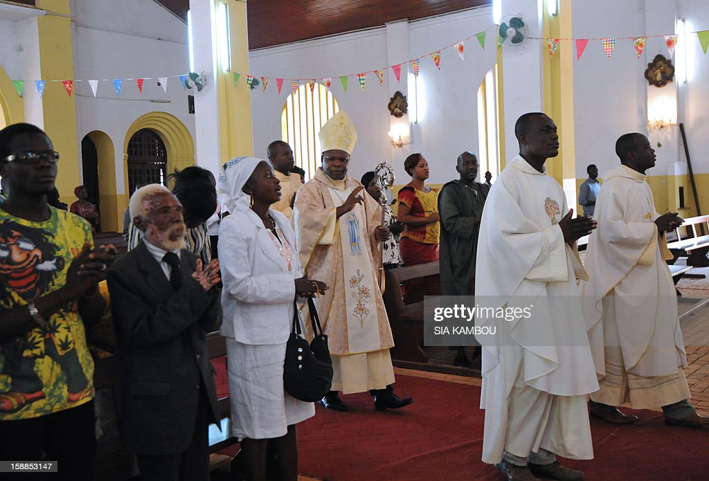 Dieudonne Nzapalainga, bishop of Bangui (C), arrives at the cathedral in Bangui to conduct a mass, on January 1, 2013. The death of a young Muslim man arrested for alleged links to rebels in the Central African Republic sparked clashes on January 1, 2013 in the capital that killed a policeman, a police source said. The unrest erupted as countries in the region sent reinforcements to protect the capital Bangui from rebels who control much of the country and are demanding the departure of President Francois Bozize.