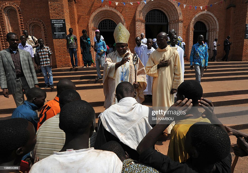 Dieudonne Nzapalainga, bishop of Bangui (C), blesses people in front of the Notre Dame de l Immaculee Conception cathedral in Bangui, on January 1, 2013. The death of a young Muslim man arrested for alleged links to rebels in the Central African Republic sparked clashes on January 1, 2013 in the capital that killed a policeman, a police source said. The unrest erupted as countries in the region sent reinforcements to protect the capital Bangui from rebels who control much of the country and are demanding the departure of President Francois Bozize.