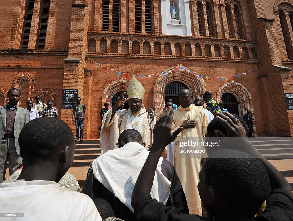 Dieudonne Nzapalainga, bishop of Bangui (C), blesses people in front of the cathedral in Bangui, on January 1, 2013. The death of a young Muslim man arrested for alleged links to rebels in the Central African Republic sparked clashes on January 1, 2013 in the capital that killed a policeman, a police source said. The unrest erupted as countries in the region sent reinforcements to protect the capital Bangui from rebels who control much of the country and are demanding the departure of President Francois Bozize.