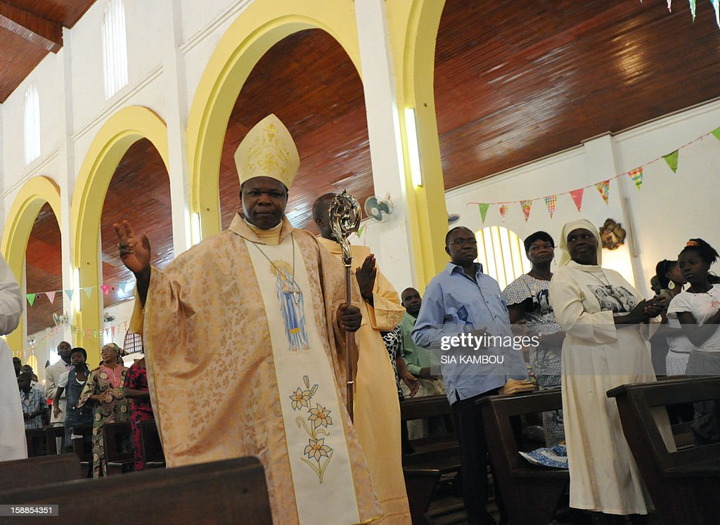 Dieudonne Nzapalainga, bishop of Bangui (L), gestures as he arrives at the cathedral in Bangui to conduct a mass, on January 1, 2013. The death of a young Muslim man arrested for alleged links to rebels in the Central African Republic sparked clashes on January 1, 2013 in the capital that killed a policeman, a police source said. The unrest erupted as countries in the region sent reinforcements to protect the capital Bangui from rebels who control much of the country and are demanding the departure of President Francois Bozize. AFP PHOTO/ SIA KAMBOU
