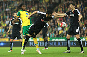 Dieumerci Mbokani of Norwich City challenges Miguel Angel Britos of Watford during the Barclays Premier League match between Norwich City and Watford...