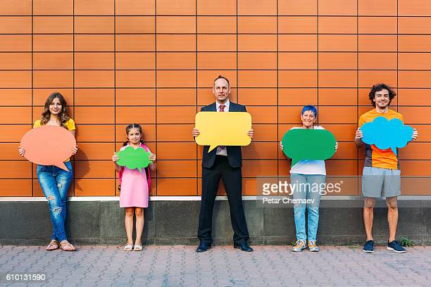 Different ages people holding colorful speech bubbles