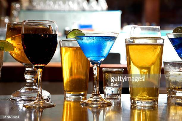 Different alcohol drinks sitting on a bar