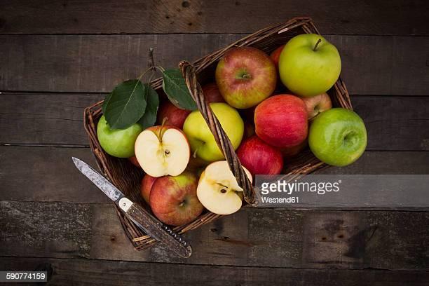 Different apples, basket and pocket knife on wood