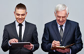 Young businessman using digital tablet and senior businessman taking notes in personal organizer