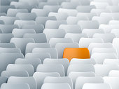 Yellow chair in a lecture hall full of white ones. Individuality, discrimination and contrasts concept
