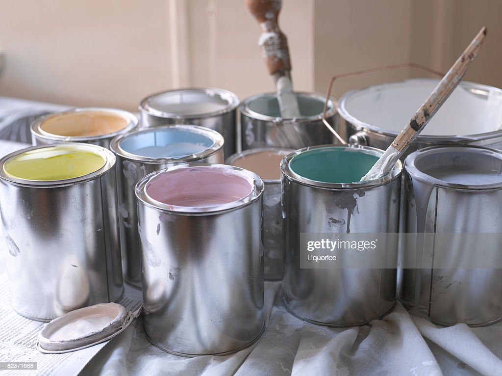different coloured paint pots with lids off : Stock Photo