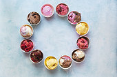 Different cups of ice cream flavors set in circle shape on rustic background with copy space, top view