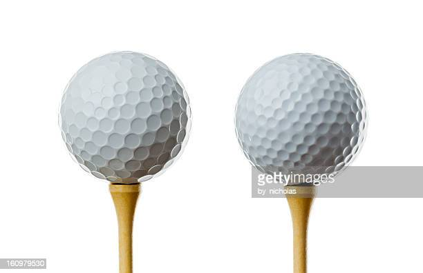 Different golf balls, on tees