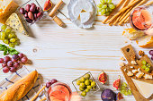 Different kinds of cheeses, wine, and snacks on the white wooden table. Shot from above with free text space.