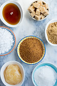 Different Kinds of Sugar and Sweeteners in the Bowls, such as coconut, pure cane, icing, maple syrup, dark brown soft sugar, honey, demerara cubes