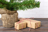 Different New Year's gifts wrapped in wrapping paper under the Christmas tree branch.