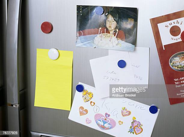 different notes pinned on door of refrigerator