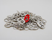 single red coloured ring pull amongst silver coloured pulls
