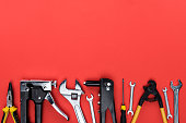 Top view shot of different reparement tools - wrenches, pliers, industrial stapler, isolated on red