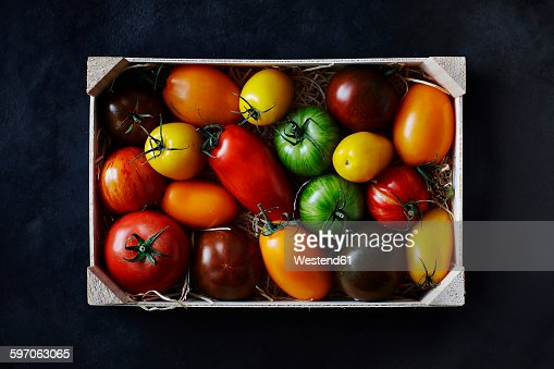 Different tomatoes in wooden box