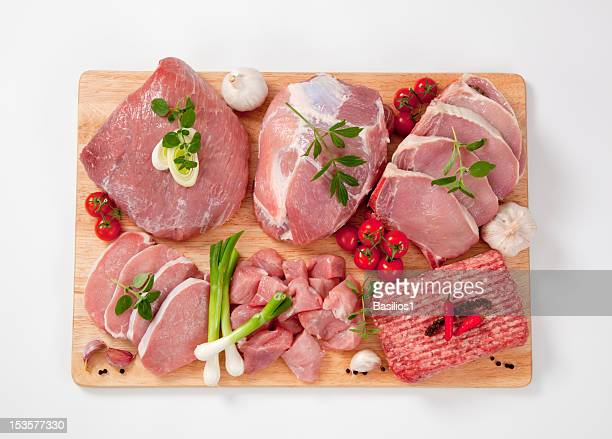 Different type of raw meat on a chopping board, garnished