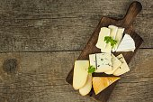 Different types of cheese on a wooden cutting board. Dairy products. Milk processing. Diet food