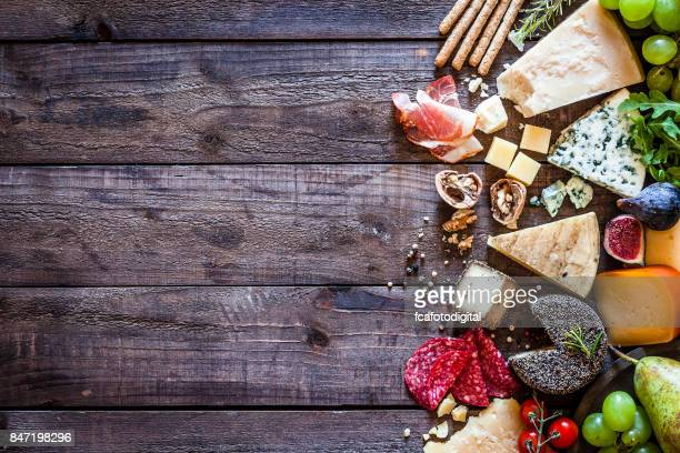 Different types of cheeses on rustic wood table
