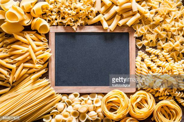 Different types of Italian pasta making a frame around a blank blackboard