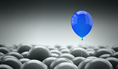 Different, unique and standing out of the crowd concept. A blue baloon is different and above the other gray ones, representing the individuality in the masses.