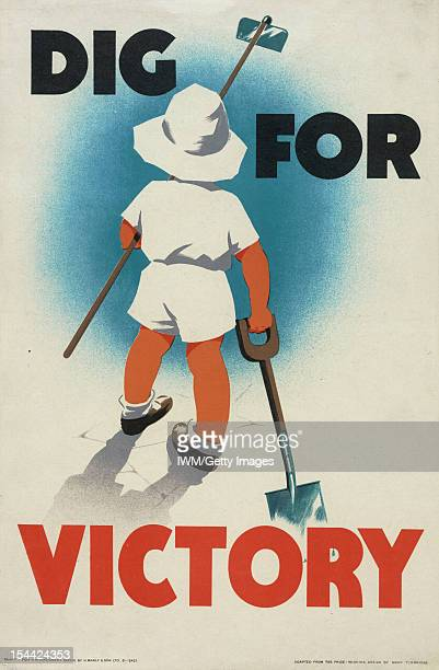 Dig For Victory Rear view of a small boy wearing a white hat white shorts and white shirt He is holding a spade in his right hand and a hoe in...