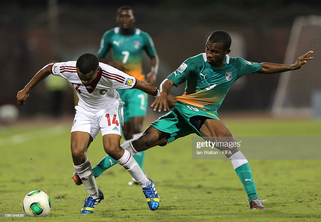 Digbo Maiga of Ivory Coast tries to tackle Omar Arjoune of Morocco during the Round of 16 match of the FIFA U-17 World Cup between Morocco and Ivory Coast at Fujairah Stadium on October 29, 2013 in Fujairah, United Arab Emirates.
