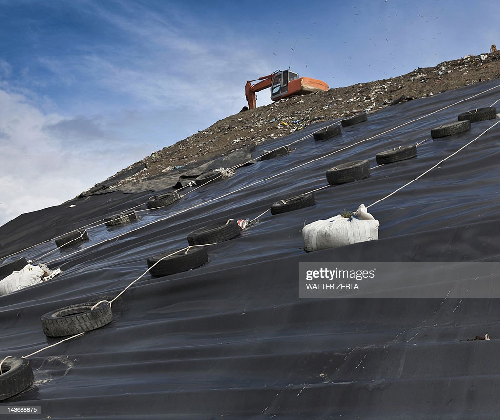 Digger at garbage collection center : Stock Photo