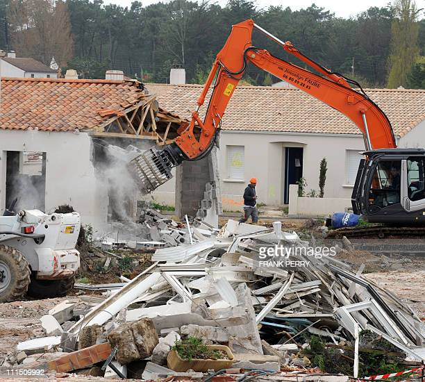 A digger bulldozer destroys an house on March 31 2011 in La FautesurMer western France during the demolition work ordered in the black zone following...