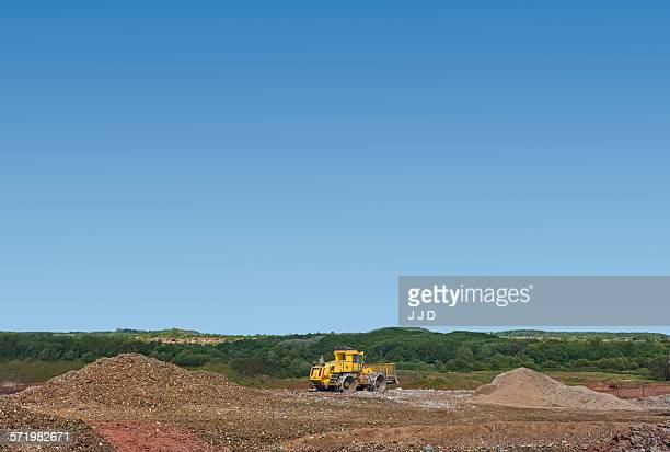 Digger burying waste on landfill site