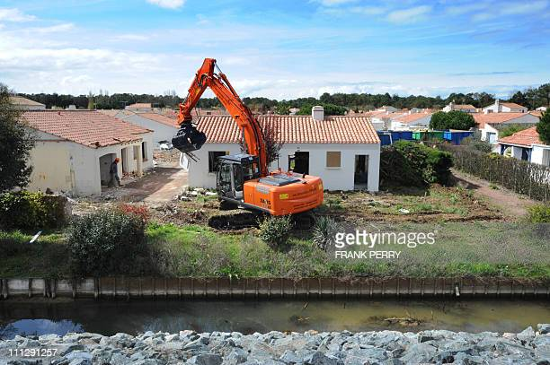 A digger cleans the rubble on the compound of the first on 95 houses on March 28 2011 in La FautesurMer western France at the first day of the...