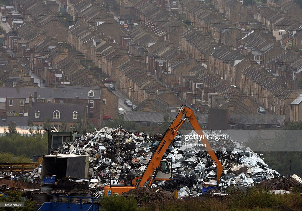 A digger, manufactured by Liebherr-International Deutschland GmbH, operates in a scrap metal yard as rows of residential terrace housing stand beyond in Newcastle-upon-Tyne, U.K., on Wednesday, Sept. 11, 2013. U.K. house prices rose for a seventh month in August and will probably continue to increase through the rest of the year, according to a report by Halifax. Photographer: Nigel Roddis/Bloomberg via Getty Images