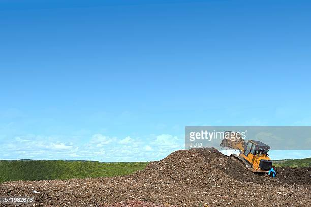 Digger on mound burying waste on landfill site