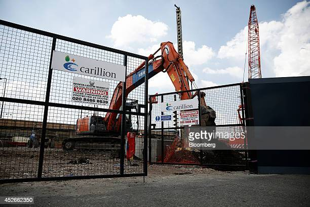 A digger operates near the gates of a construction site for new apartment blocks built by Carillion Plc in the Canning Town district of London UK on...