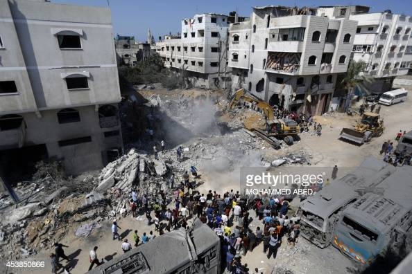 A digger removes on August 20 the cement and debris of a home destroyed the night before in an Israeli air strike on Gaza City's Sheikh Radwan...