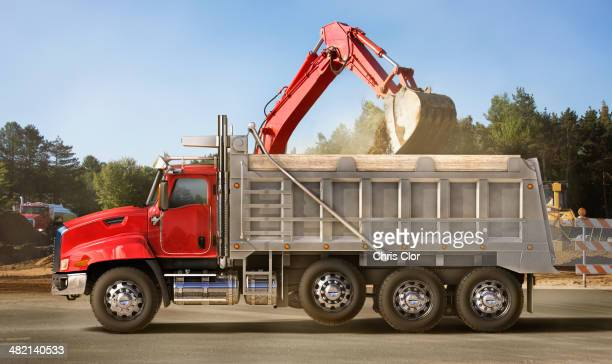 Digger scooping into dump truck on site