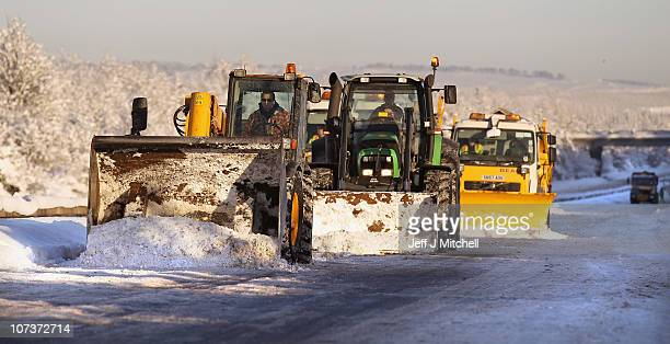 Diggers and snow ploughs attempt to clear the west bound M8 Motorway which connects Scotland's two biggest cities Glasgow and Edinburgh on December 7...